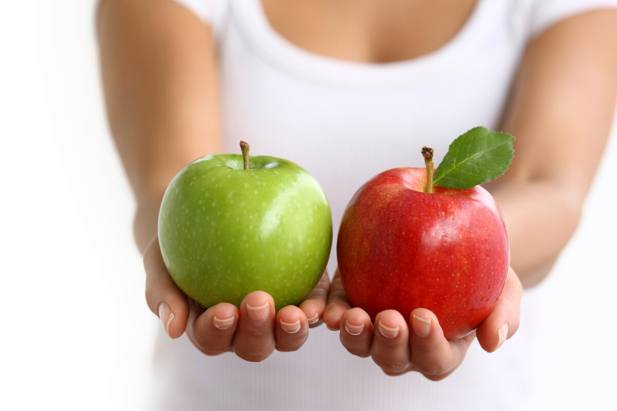 woman holding green apple next to red apple