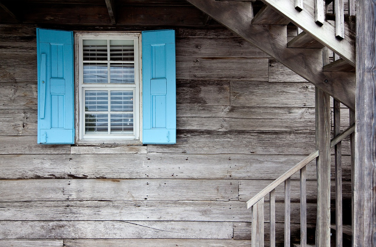 blue storm shutters on old wooden house