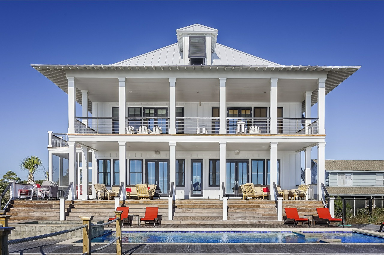 large white rental house with pool and pillars