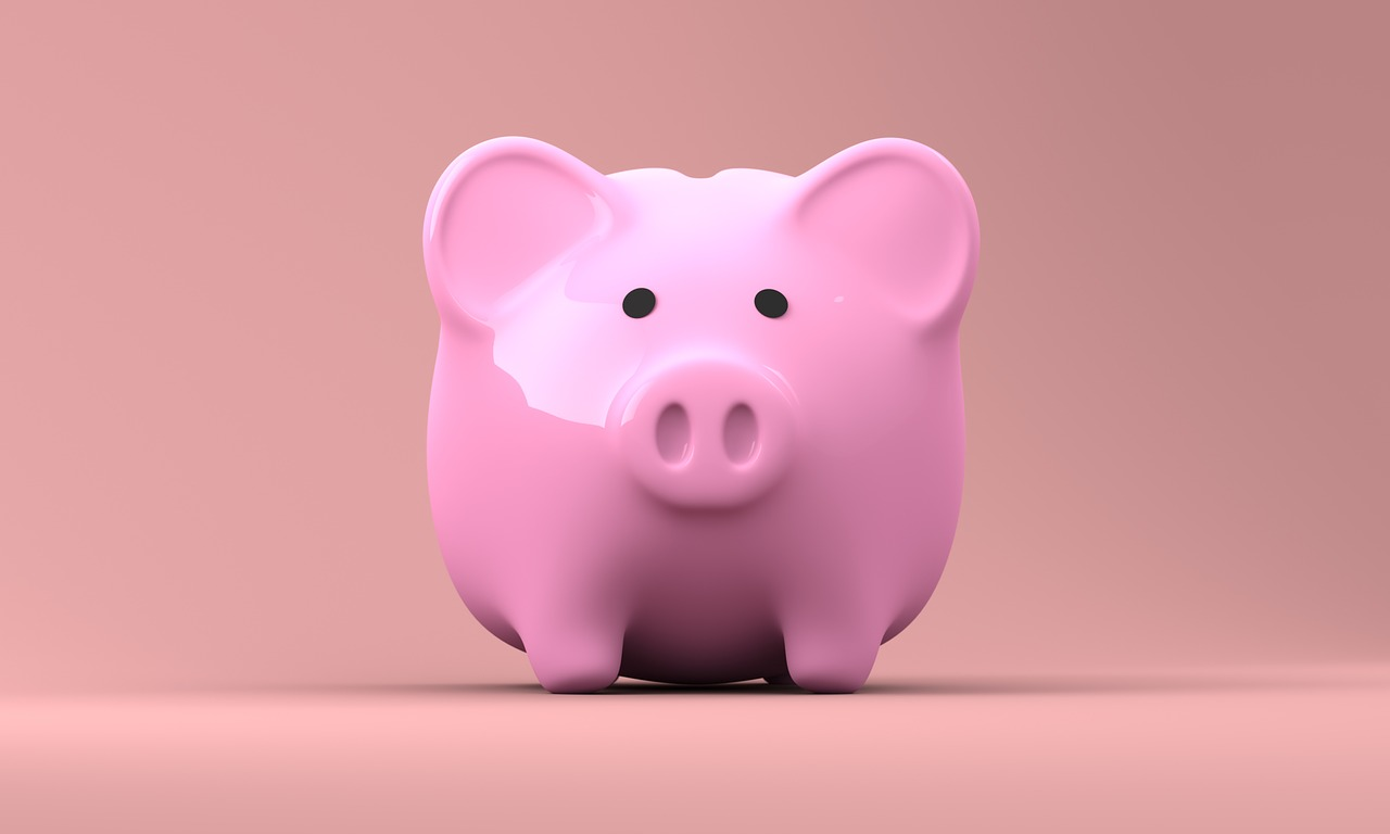 shiny pink piggy bank on pink background