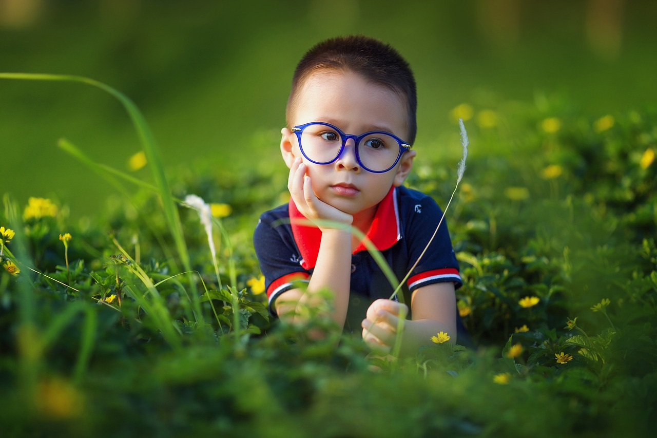 young boy thinking in grassy field with blue rimmed glasses