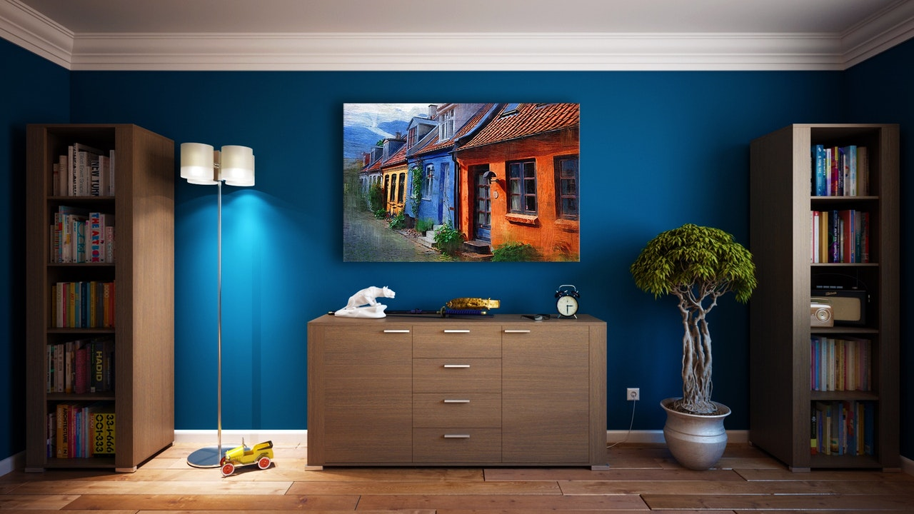 colorful painting on blue wall with furniture all around