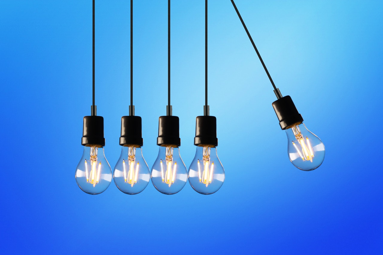 five light bulbs hanging in front of blue background