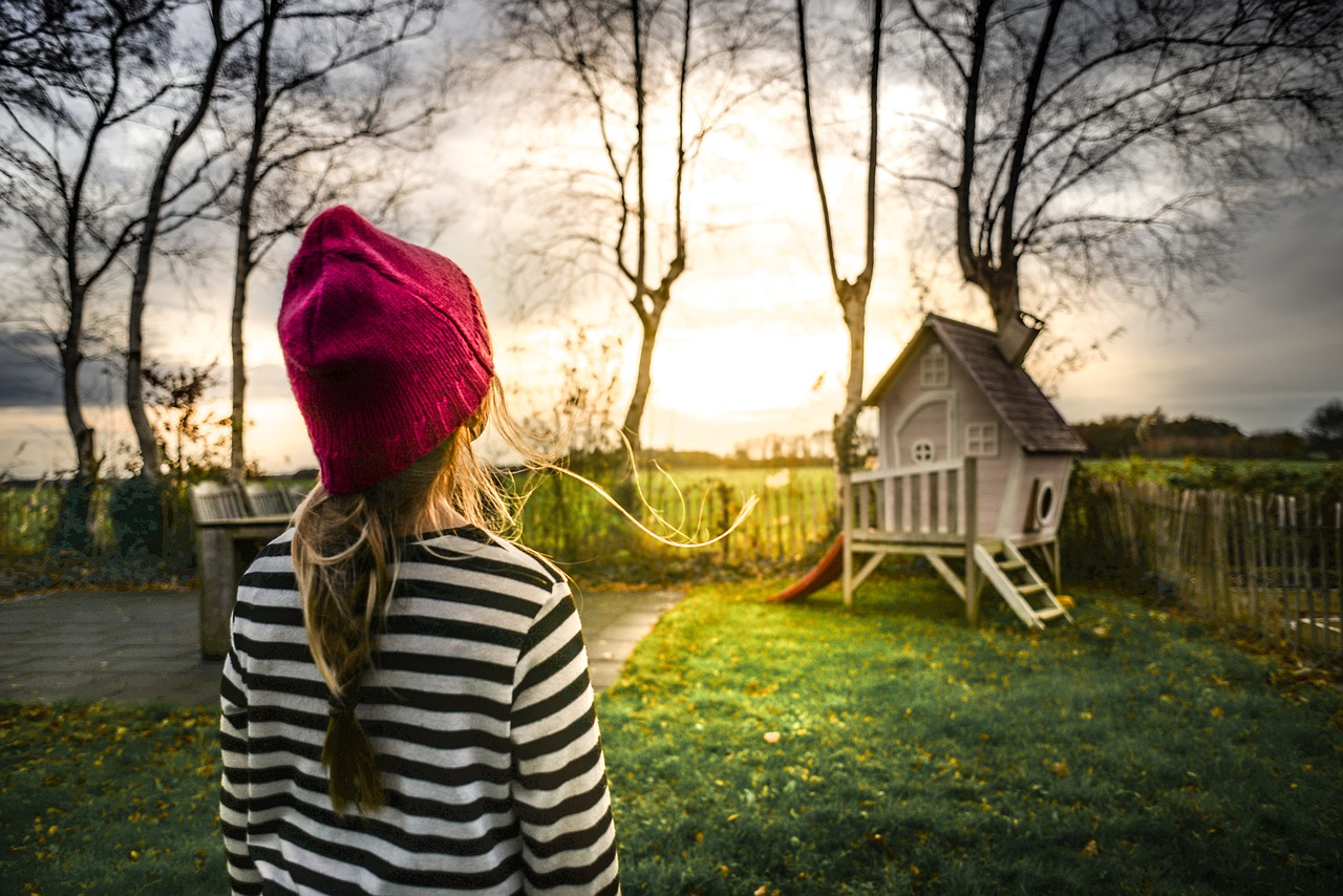 young girl looking at playhouse in backyard at sunrise