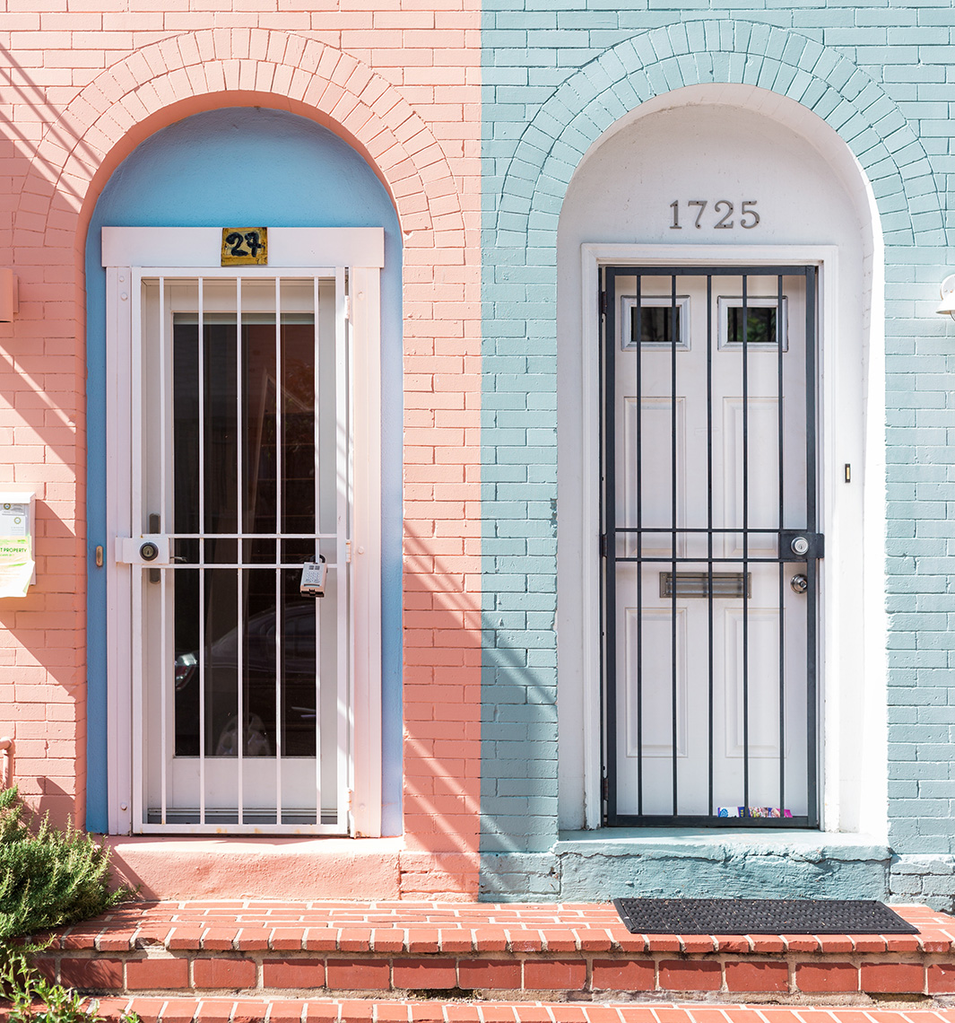 two town home doors in pink and blue brick