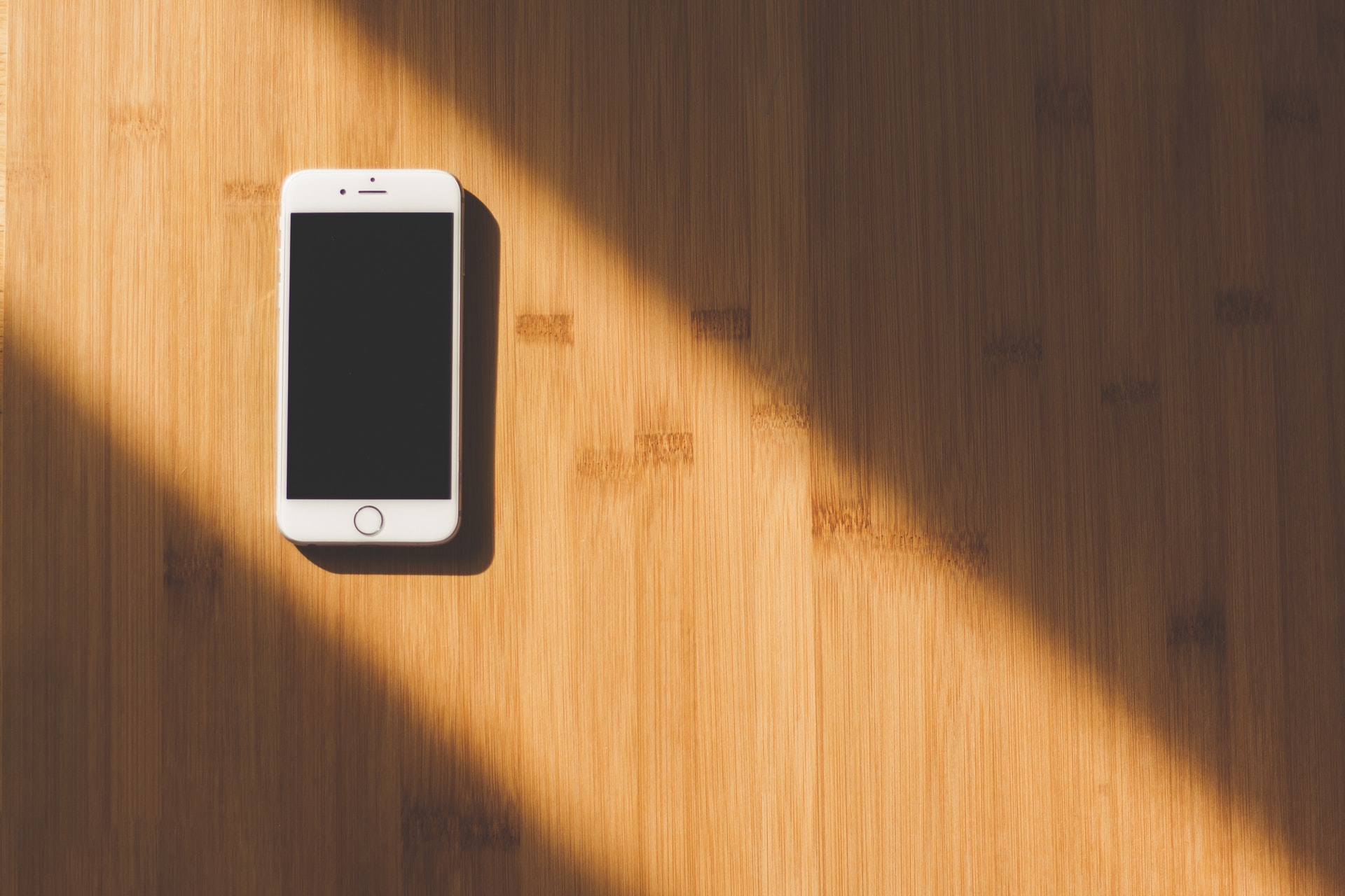 smart phone on wooden desk in sun beam