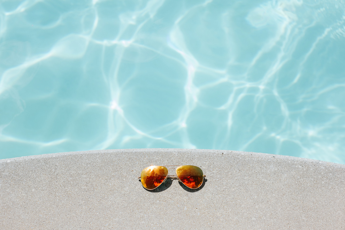 orange sunglasses by side of pool