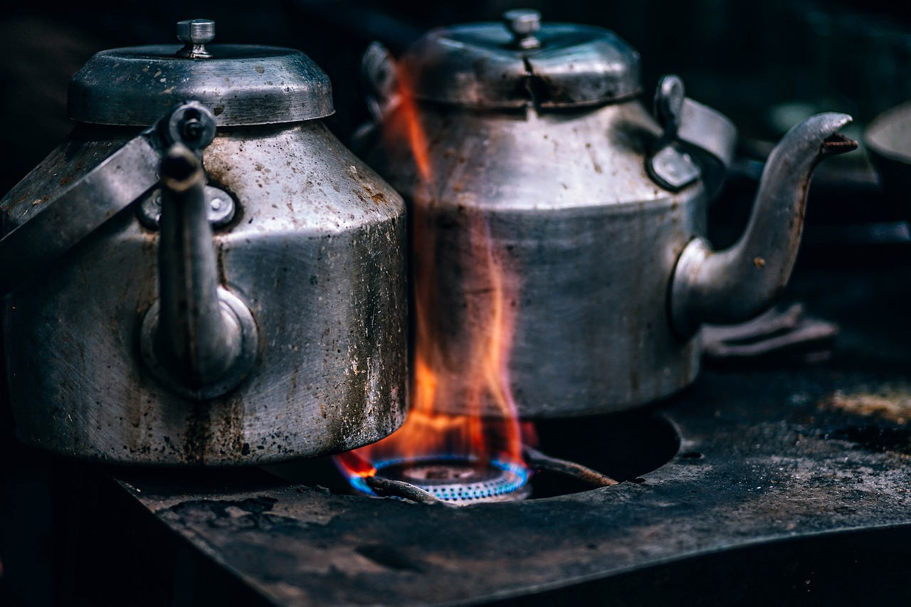 two iron kettles over orange flame