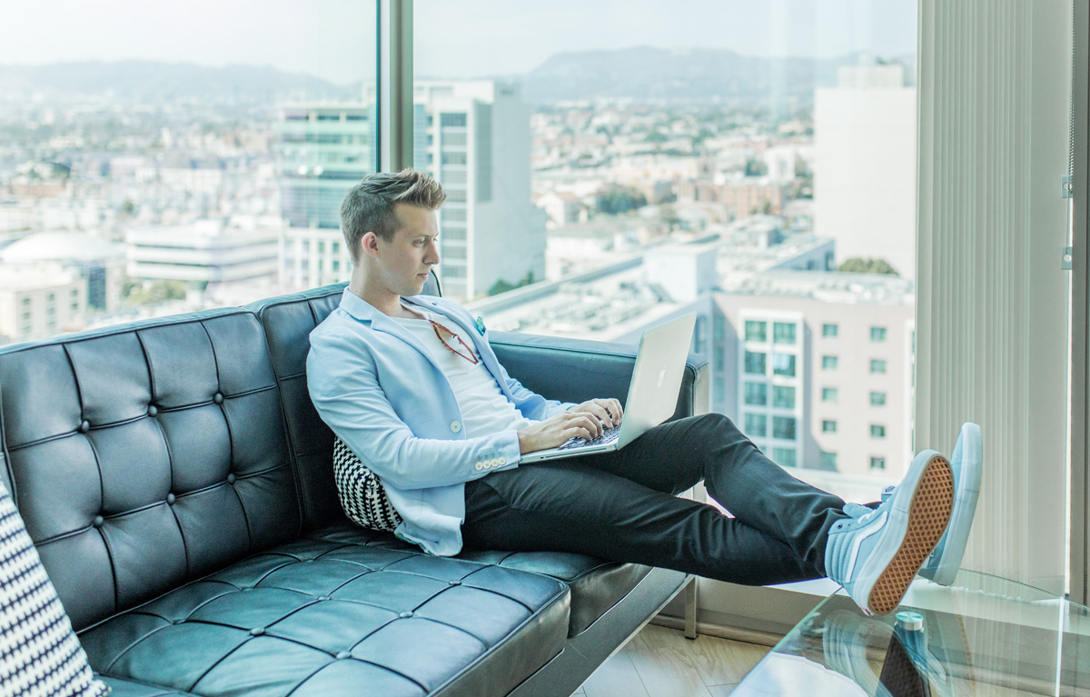 man on couch working on computer
