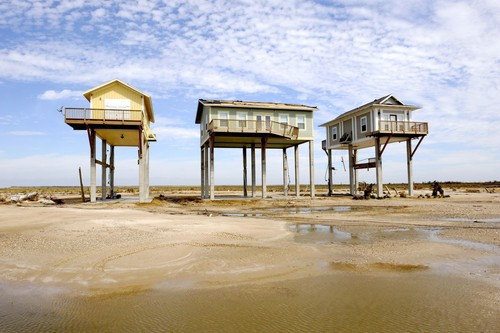 three houses on beach raised on stilts